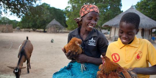 Maria Francisco Mutuque mit einem ihrer Söhne und Hühnern. (Foto: Abbie Trayler-Smith/ Oxfam Australia)