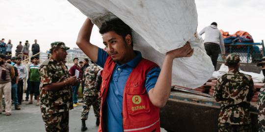 Shekhou Khadka (23) ist einer von 500 lokalen Freiwilligen, die Oxfam für Katastrophenfälle geschult hat. Hier entlädt er  mobile Latrinen für eine der provisorischen Zeltstädte in Kathmandu. (Foto: Aubrey Wade/ Oxfam)