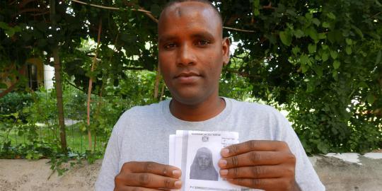 Osman M. mit einem Bild seiner Frau. © Helena O'Donnell/Oxfam
